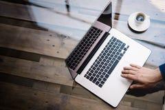 Mężczyzna używa laptop przy pogodnym biurem Męskiej ręki notatnika wzruszający trackpad Nowożytny notatnik, filiżanka czarna kawa Zdjęcia Stock