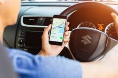Mężczyzna używa mapy podaniowe na iphone i napędowym suzuki jerzyka samochodzie Fotografia Royalty Free