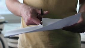 Mężczyzna używa nożycowych cięcia biały papier zbliżenie zdjęcie wideo