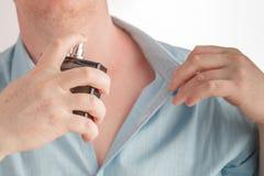 Mężczyzna używa pachnidło na białym tle fotografia stock