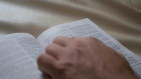 Mężczyzna używa ręki trzepnięcia książki czytać Zakończenie up otwarta książka z stron podrzucać Strona biblia, zakończenie zbiory wideo