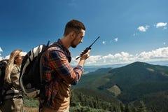 Mężczyzna używa radio podczas górskiej wycieczki z kobietą zdjęcie stock