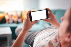 Mężczyzna używa smartphone horyzontalnego na kanapie fotografia royalty free