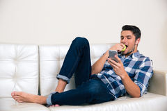 Mężczyzna używa smartphone i jedzący jabłka Obrazy Stock