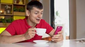Mężczyzna używa smartphone podczas gdy pijący kawę zdjęcie wideo