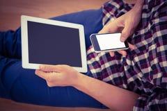 Mężczyzna używa smartphone podczas gdy trzymający cyfrową pastylkę Obrazy Royalty Free