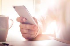 Mężczyzna używa smartphone przy biurem Obrazy Stock