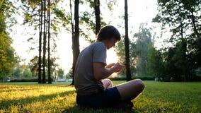 Mężczyzna używa smartphone w parku przy zmierzchem podczas gdy siedzący na trawie zdjęcia royalty free