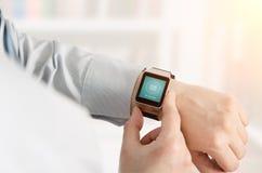 Mężczyzna używa smartwatch z e-mailowym notifier Obraz Royalty Free