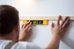 Mężczyzna używa spirytusowego poziom w domu Obrazy Stock