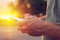 Mężczyzna używa telefon komórkowego na ulicie w zmierzchu Zdjęcia Stock