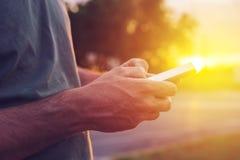 Mężczyzna używa telefon komórkowego na ulicie w zmierzchu Obraz Royalty Free