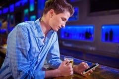 Mężczyzna używa telefon komórkowego przy baru kontuarem Zdjęcie Royalty Free