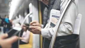 Mężczyzna używa telefon komórkowego w metro pociągu obraz royalty free