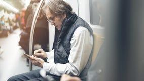 Mężczyzna używa telefon komórkowego w metro pociągu zdjęcia stock