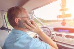 Mężczyzna używa telefon podczas gdy jadący samochód Zdjęcie Royalty Free