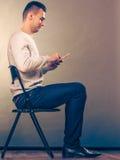 Mężczyzna używa telefonu komórkowego obsiadanie w krześle Zdjęcia Stock