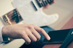 Mężczyzna używa urządzenie przenośne i gitarę Obrazy Royalty Free