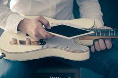 Mężczyzna używa urządzenie przenośne i gitarę Zdjęcia Stock