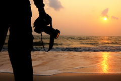 Mężczyzna używają kamerę brać obrazki wschód słońca Obrazy Stock