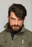 Mężczyzna ubierał w khakiej kurtce z ciekawym spojrzeniem zakończenie W górę greaser Obraz Stock