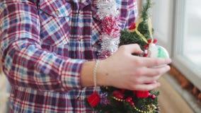 Mężczyzna ubiera pięknej małej rozjarzonej choinki zbiory wideo