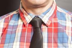 Mężczyzna Ubierająca W kratkę koszula Z czarnym krawatem Na szarość obrazy royalty free
