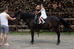 Mężczyzna uczy dziewczynom przejażdżka konia na drewnianym sterty tle zdjęcie stock