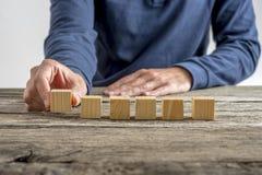 Mężczyzna umieszcza sześć pustych drewnianych sześcianów z rzędu Obraz Stock