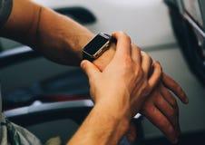 Mężczyzna use jego mądrze zegarek w samolocie Obrazy Stock