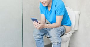 Mężczyzna use telefon na toalecie zdjęcie royalty free