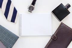 Mężczyzna ustawiający: zegarek, krawat, krawat klamerka, pióro, pachnidło, portfel i notepad, zdjęcie royalty free