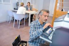 Mężczyzna utrzymuje biurowego photocopier obraz stock
