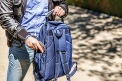 Mężczyzna utrzymuje jego telefon komórkowego w jego błękitnym plecaku zdjęcia royalty free