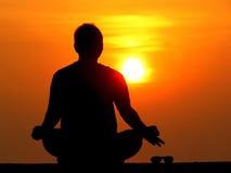 Mężczyzna utrzymuje na boku jego okulary przeciwsłonecznych na boku i medytuje na r Fotografia Stock