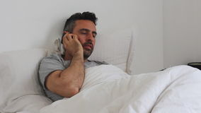 Mężczyzna w łóżkowym use jego smartphone zdjęcie wideo