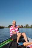 Mężczyzna w łodzi przy rzeką Obrazy Royalty Free