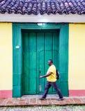 Mężczyzna w żółtej koszula z ruch plamą chodzi past zieleni drzwi Zdjęcia Stock
