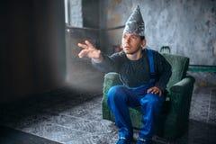 Mężczyzna w aluminiowej folii hełmie dosięga out TV zdjęcie royalty free