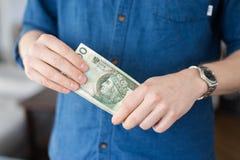 Mężczyzna w błękitnym przypadkowym koszulowym mienie połysku pieniądze obraz royalty free