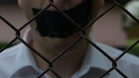 Mężczyzna w białej koszula jest za siecią i zakrywa jego usta z scotch taśmą, wyjawienie informacja, wolność zdjęcie wideo