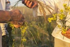 Mężczyzna w białej tradycyjnej Slawistycznej sukni i dziewczyna wreathes wianek świezi wildflowers przy zmierzchem Rosyjskie trad obraz stock