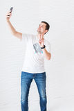 Mężczyzna w białych niebieskich dżinsach i koszulce robi selfie na białym tle i przedstawieniach gestykulować Â 'peaceÂ' Zdjęcie Stock