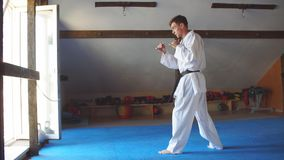 Mężczyzna w białym kimonie z czarnego paska stażowym karate w gym zbiory