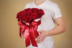 Mężczyzna w białym t koszulowym mieniu w ręka prezenta bogatym bukiecie 21 czerwień Obrazy Royalty Free