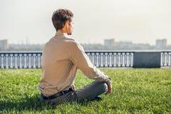 Mężczyzna w biurowym kostiumu medytuje na zielonym gazonie Zdjęcia Stock