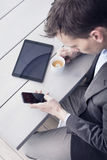 Mężczyzna w biurowym używa smartphone Fotografia Royalty Free