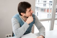 Mężczyzna w biurze siedzi przy stołem, słucha attentively i jego rękach i pustym prześcieradle papier z piórem w zdjęcia stock