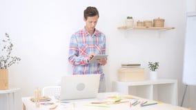Mężczyzna w biurze używać elektroniczną pastylkę, kreatywnie projektant, agencja Fotografia Royalty Free