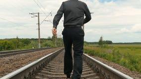 Mężczyzna w biznesów ubraniach biega wzdłuż kolejowych śladów swobodny ruch zbiory wideo